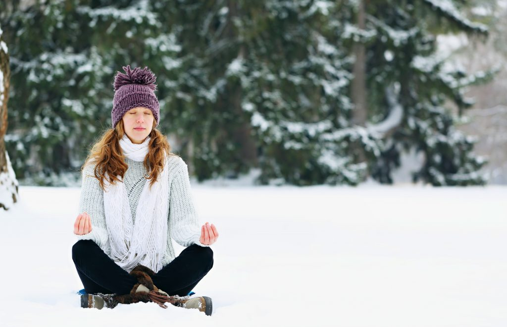 Young woman sitting and meditating at the park in winter